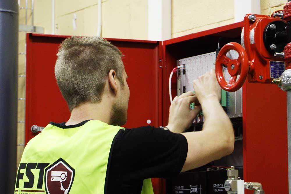 Niklas sätter upp ett anpassat brandlarm för en klient - FST Säkerhet